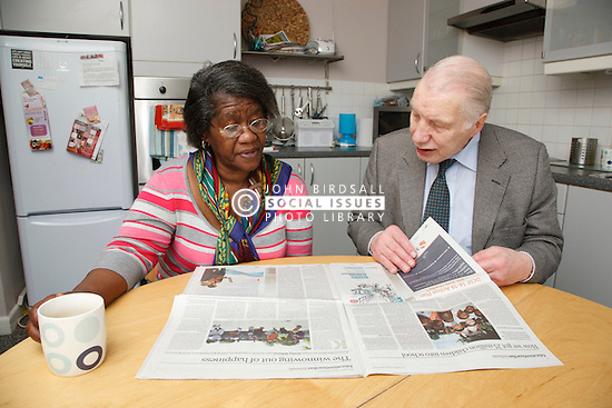 Carer and pensioner talking over newspaper.