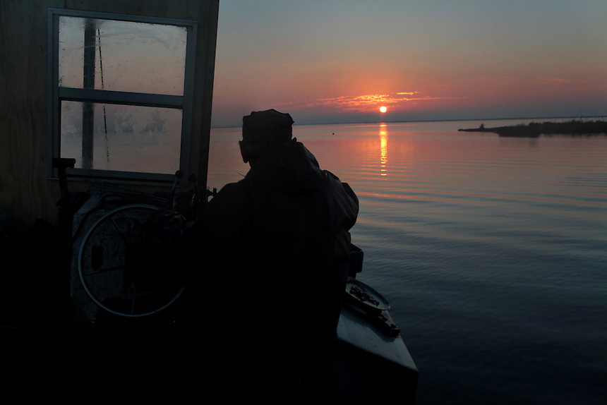 Thomas Gonzales watches the sun rise while crab fishing in Delacroix, LA on November 12, 2010.