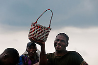 A Colombian man shows joyfully a basket full of shellfish collected in the mangrove swamps on the Pacific coast, Colombia, 12 June 2010. Deep in the impenetrable labyrinth of mangrove swamps on the Pacific seashore, hundreds of people struggle everyday, searching and gathering a tiny shellfish called 'piangua'. Wading through sticky mud among the mangrove tree roots, facing the clouds of mosquitos, they pick up mussels hidden deep in mud, no matter of unbearable tropical heat or strong rain. Although the shellfish pickers, mostly Afro-Colombians displaced by the Colombian armed conflict, take a high risk (malaria, poisonous bites,...), their salary is very low and keeps them living in extreme poverty.
