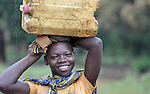 A girl in Riimenze, a village in Southern Sudan's Western Equatoria State, prepares to carry a jerry can of water home from a well.