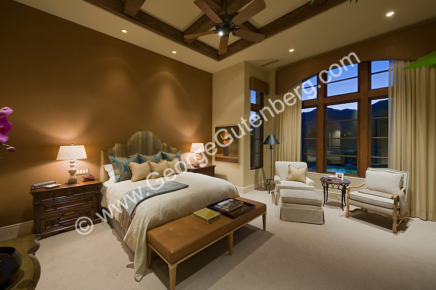 Elegant master suite with wood beamed ceiing and large window showing night sky