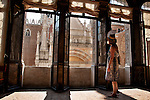 A woman in a sun dress admires the view from inside the Doge's Palace in Venice, Italy