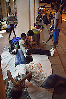 Italy. Lombardy Region. Como. Homeless african migrants sleep at night in the San Giovanni railway station. Eritrean men lie down on the ground. 10.08.2016 © 2016 Didier Ruef