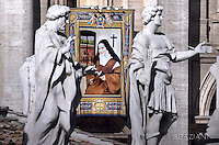 """A tapestry hanged on the facade of St Peter's basilica shows a portrait of French Elizabeth of the Trinity during a canonization mass.Pope Francis  leads a canonization mass on October 16, 2016 at St Peter's square in Vatican. Pope Francis canonises Argentine """"gaucho priest"""" Jose Gabriel Brochero today along with six others raised to sainthood : Salomon Leclercq, Jose Sanchez del Río, Manuel Gonzalez Garcia, Lodovico Pavoni, Alfonso Maria Fusco and Elizabeth of the Trinity."""