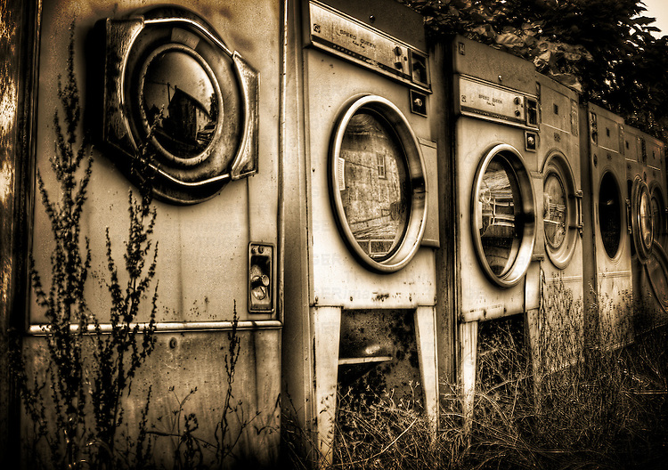 Redundant washing machines in a row left outside with grass growing