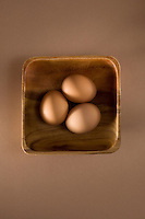 Three brown eggs wooden bowl in studio brown background.