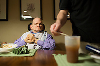 Frank Bandolfh, 56, (left) sits at a table for dinner as Kevin Calahane, LPN, feeds resident David Gilmore, 66, (not pictured), at an assisted living home run by Northeast Residential Services in Bedford, Massachusetts, USA.  The residents previously lived at the Fernald Developmental Center in Waltham, Massachusetts, USA.