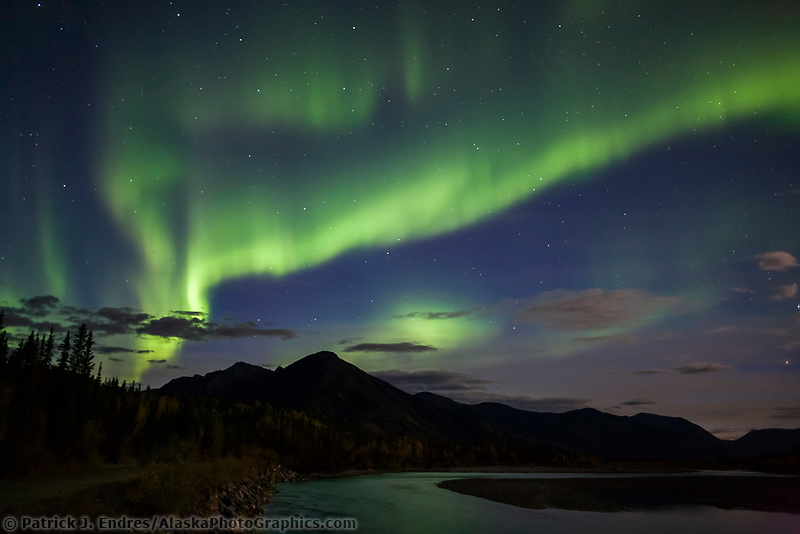 Green aurora borealis (northern lights) over the Koyukuk river, Midnight Dome mountain, and the Brooks range mountains, Arctic, Alaska.
