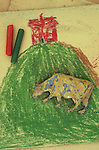 Childs crayon drawing of steep grassy hill with brown path leading to typical house with wax crayons and scratched lead model of cow lying on top
