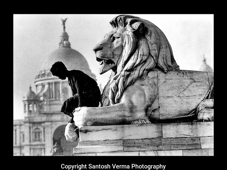 A street child descending from the seemingly strong arms of a marble lion that guard and adorn the gates of Victoria Memorial in the background, Kolkatta. Photograph © Santosh Verma