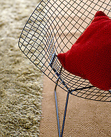 A wire-mesh Bertoia armchair with a bright red cushion in the living room of a Florida home