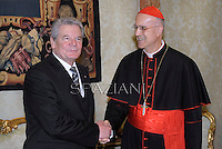 Cardinal Tarcisio Bertone  and German President Joachim Gauck exchange gifts during a private audience on December 6, 2012 in the pontif's library at the Vatican