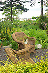 two wicker armchairs sit in a hidden lookout spot of a waterside woodland garden surrounded by lush summer woodland gardens