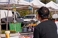 A man drinks coffee and relaxes while eating at South Coast Collection's Farmers' Market.