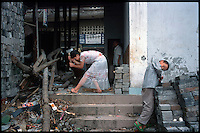 Fengdu, China, August 2003.A little girl chopping wood in the old city of Fengdu, already half-destroyed to allow the Three Gorges Dam project to be completed.