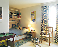In this child's bedroom the bed has been tucked cosily into an alcove with built-in bookshelves above making the most of the light and space