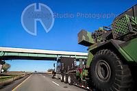 Americana Series: Road Trip<br /> <br /> Military vehicle painted camouflage green with large tire against a clear blue sky