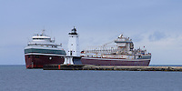 The Freighter Wilfred Sykes passes the Ludington Light as it enters port.