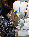 March 17, 2011, Koriyama, Japan - Medical staff in protective gear check radiation levels on local residents in Koriyama, Fukushima prefecture, on Tuesday, March 15, 2011. A nuclear power plant, located along the Pacific coast some 35km southeast of Koriyama, has had a series of trouble in its reactors since a magnitude 9.0 earthquake hit northeastern Japan on March 11. (Photo by AFLO) [3609] -mis-