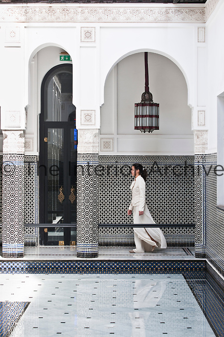A member of staff walking through the black and white courtyard
