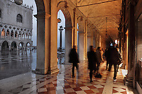 The Doric arcades of the Biblioteca Nazionale Marciana, or National Library of St Mark's, built in Renaissance style in 1537-53 by Jacopo Sansovino, then extended by Vincenzo Scamozzi in 1588, on the Piazzetta San Marco, between the Piazza San Marco and the Venetian lagoon, Venice, Italy. The library houses an important collection of classical, Oriental and medieval codices and manuscripts. Through the arch is the Column of San Marco, with a statue of St Mark the evangelist in the form of a winged lion, 12th century, by Nicolo Barattieri. To the left is the Doge's Palace or Palazzo Ducale, begun 1340 and built in Venetian Gothic style. The historical centre of Venice is listed as a UNESCO World Heritage Site. Picture by Manuel Cohen