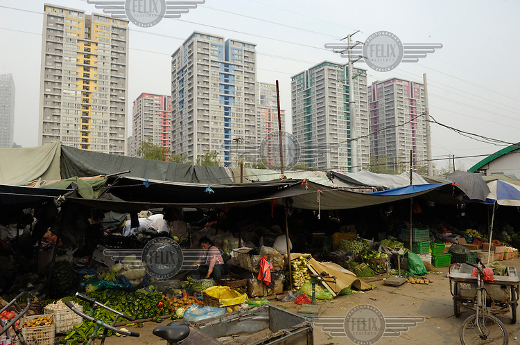 Market stalls close by to luxury 'New Town SOHO' residential and commercial complex in Jianguomen.