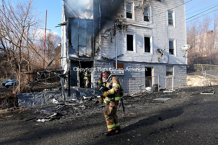 Waterbury, CT- 11 April 2015-041115CM17-   A Waterbury firefighter takes a moment while fighting a fire on Orange Street in Waterbury on Saturday.  An afternoon fire destroyed a multifamily house.   Christopher Massa Republican-American