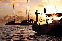Man stretching on yacht at sunrise in lagoon off Tahaa Island