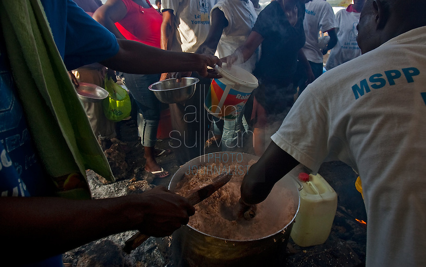 Afternoon meals of beans and rice are distributed in Jacmel's Pechinat camp for displaced persons. The 7.0 earthquake that devastated parts of Haiti on January 12 killed hundreds of thousands of people. January's earthquake killed hundreds of thousands of people and caused significant and lasting structural and economic damage in the Caribbean nation.