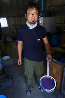Staff holds indigo dye. Nihon Menpu, Ibara City, Okayama Prefecture, Japan, July 10, 2013. Kojima is the birthplace of Japanese denim and famous for artisan jeans. The area's textile industry is based on advanced dyeing and weaving technology that has it's roots in pre-industrial indigo dyeing.