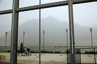 Italy. Lombardy region. Campione d'Italia. A mother and her child in a push-chair walk on the sidewalk in the winter season. Electric lights. Reflection on the Monte Generoso from the glass window's front of the old derelict Casino Municipale. Campione d'Italia is occupying an enclave within the Swiss canton of Ticino, separated from the rest of Italy by Lake Lugano and mountains. Campione d'Italia takes advantage of its status by operating a famous casino, the Casinò di Campione, as gambling laws are less strict than in both Italy and Switzerland. The new Casinò di Campione was opened in 2007. It is the largest gambling place in Europe and replaces the existing 1936 casino. 28.02.2008 © 2008 Didier Ruef
