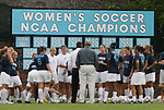 """24 September 2009: UNC head coach Anson Dorrance (in white) talks to his team before the game with their """"Women's Soccer NCAA Championship"""" banners as a backdrop. The University of North Carolina Tar Heels defeated the Duke University Blue Devils 2-1 in sudden victory overtime at Fetzer Field in Chapel Hill, North Carolina in an NCAA Division I Women's college soccer game."""