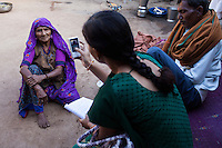 An upper caste family listens as Video Volunteer videojournalist Niru J. Rathod, 24, does spot interviews with their family members in their home on topics of caste discrimination and water quality issues in a remote village in Surendranagar, Gujarat, India on 14 December 2012. The last time Niru had come to their home, she was discriminated against and served tea in a saucer meant for lower castes. Now, after seeing the effects of her video activism, the family no longer discriminates against her. Niru, the 8th child in a family of 11 girls born to a Dalit construction worker, has been using videography for social change since 2006. She shoots and produces her own short documentaries and is a committed video activist, having conducted hundreds of village video screenings where she also speaks to thousands of men, shattering their ideas about what a woman and a Dalit can do while bringing massive changes to the communities she documents. Photo by Suzanne Lee / Marie Claire France