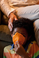 Marilyn Berger (partly visible), widow of Don Hewitt, touches Danny Hodes, the 8 year-old Ethiopian boy she has taken in, as he plays with play-doh in her apartment in New York, NY, USA, 9 April 2010. Ms Berger met him in Addis Ababa while reporting there and helped him get surgery.