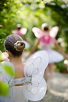 Close-up of the back of a girl dressed as fairies dancing under the rose covered archway in dappled sunlight