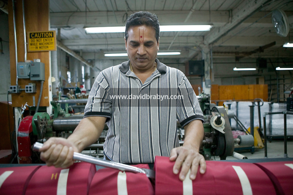 21 June 2005 - Oaks, PA - Suresh Patel separates by hand the machine-slit polyester fabric that will be turned into red stripes at the Annin & Co. American flag manufacturing plant in Oaks, PA, USA. Photo Credit: David Brabyn.