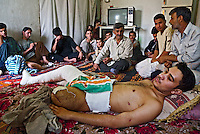 Baghdad, Iraq, June 8, 2003.Lhoi Kherala, 19, whith his father, center, and family, was severely wounded to both legs during the March 28th bombing of the Shu'ala market during wich 57 civilians were killed. 12 days and 3 operations after the event, doctors in Shahid Adnan hospital had to amputate his left leg; they only give him 40% chances to recover the use of his right leg. Lhoi is engaged to his cousin Adrah Ayad, they were supposed to get married in July, but they will delay the wedding a few months until he recovers. .