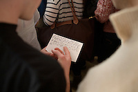 People look at a handwritten question they hope to ask Ron Paul at a rally at Jet Aviation in Nashua, New Hampshire, on Jan. 6, 2012.  Paul is seeking the 2012 GOP Republican presidential nomination.
