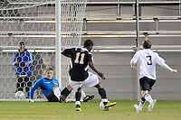 Levi Houapeu (11) of the UMBC Retrievers shoots and scores past Princeton Tigers goalkeeper Sean Lynch (1) who was down from making a save during the first round of the 2010 NCAA Division 1 Men's Soccer Championship at Roberts Stadium in Princeton, NJ, on November 18, 2010.