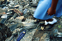 Haiti. Province of Ouest. Port-Au-Prince. Downtown. Market area. A schoolgirl, wearing a blue uniform, white socks and shiny shoes, walks on dirty garbage, old shoes and plastic bags leftover in the street . © 2003 Didier Ruef