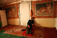 A man sits in his home at the Chalabixan settlement for people displaced from Nagorno-Karabakh near Sheki, Azerbaijan, on Wednesday, Nov. 2, 2005.
