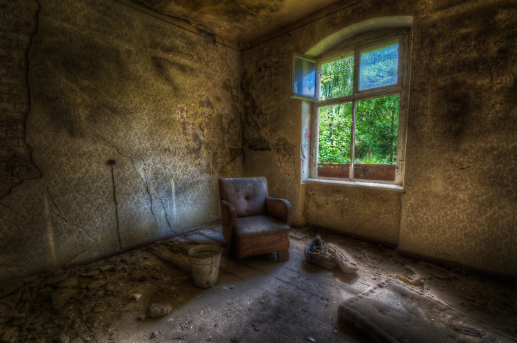 derelict room in old house in Frankfurt Oder with chair and bucket beside window