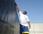 Mike Young prepares to change out wind screens at the John Leslie Tennis Courts on Thursday, August 26, 2010.