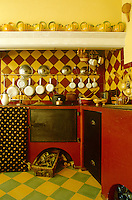 The walls and floor of this kitchen are lined in the vibrant painted earthenware tiles typical of the region and a collection of yellow and green jugs is displayed on the mantelpiece
