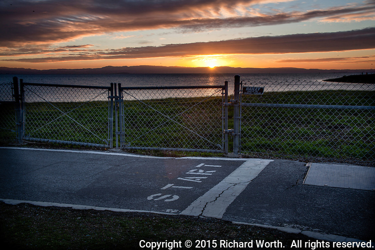 The sun sets in the distance, across San Francisco Bay, ending the day, while the foreground says START, the beginning of a measured portion of the Bay Trail.