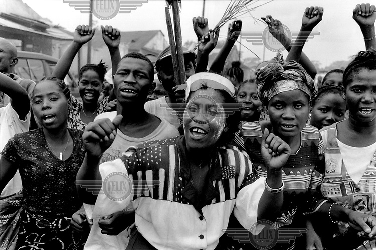 Civilians sing and dance to celebrate the victory of government forces, who had recently retaken Ganta, a small town in the north of the country, from LURD rebels..The ongoing conflict in Liberia intensified in March 2003 when rebels opposed to the government of Charles Taylor gained territory across much of the country. In August 2003 Taylor agreed to hand over power to an interim government and went into exile, which led to the signing of a peace agreement.