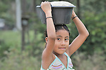A girl carries corn to be ground in Santa Elena, in Guatemala's Peten region.