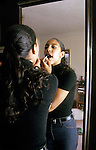 Oakland CA Girl, sixteen-years-old applying makeup in her bedroom  MR