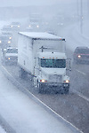 Traffic is going slow but moving as a winter snowstorm blankets Chicagoland. A white semi tractor trailer rig attempts to make it's way through to deliver its cargo.
