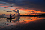 a woman paddles a kayak back toward the shore at Flamingo in Everglades National Park just after sunset.  She is sillouetted against the red tones of the sky